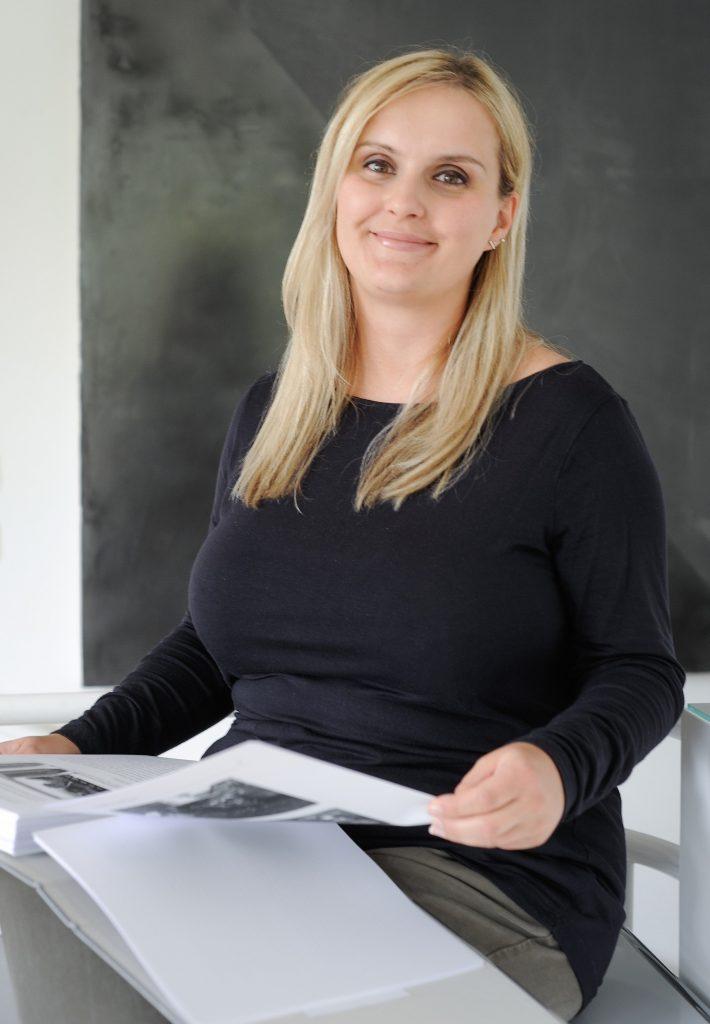 Ein Bild von unserer Rechtsanwaltsfachangstellten Alma Borovac mit einem Aktenordner in auf dem Schoß.