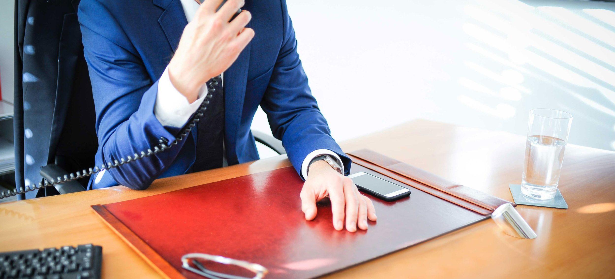Anwalt an einem Schreibtisch mit der rechten Hand an einem Telefon